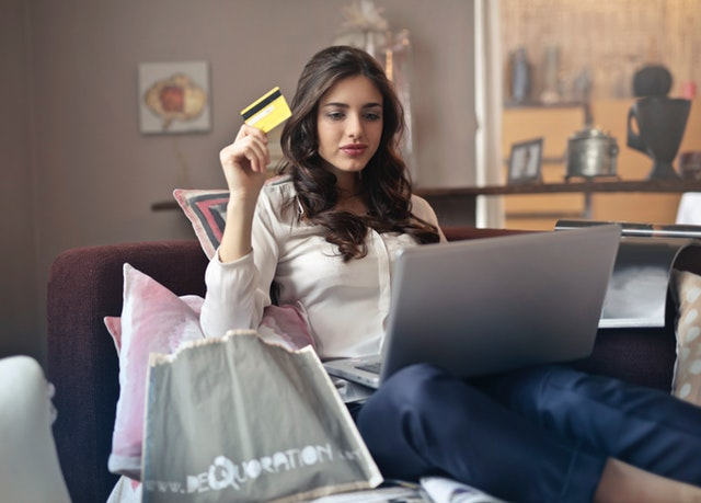 A young woman with a credit card and a laptop
